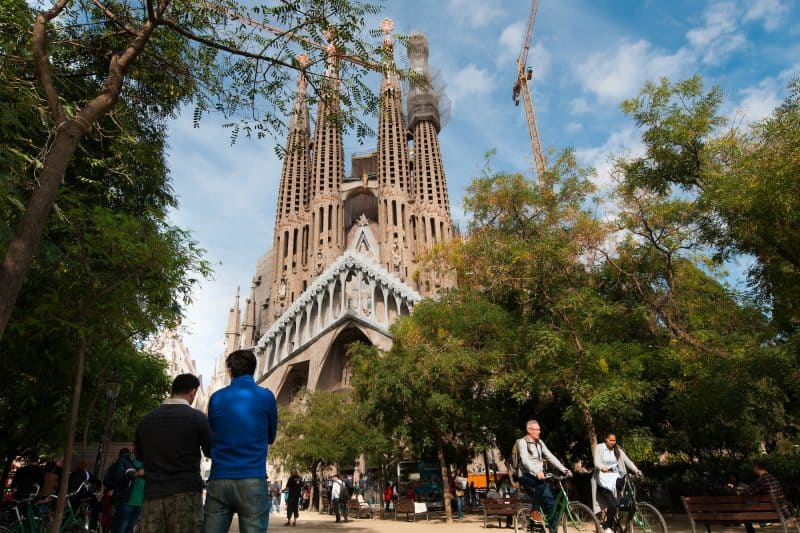 The Sagrada Familia with trees and people in front of it