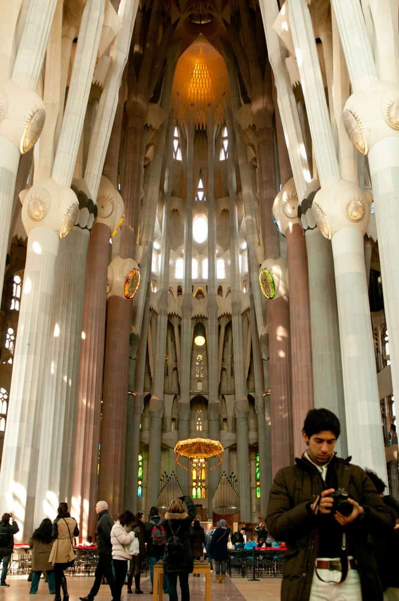 The inside of the Sagrada Familia, people making pictures and a beautiful lamp